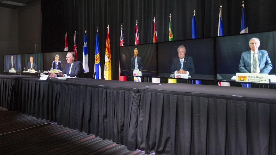 François Legault est assis tout seul à une très longue table. Derrière lui, on voit une série d'écrans de télévision sur lesquels apparaissent les premiers ministres des autres provinces.