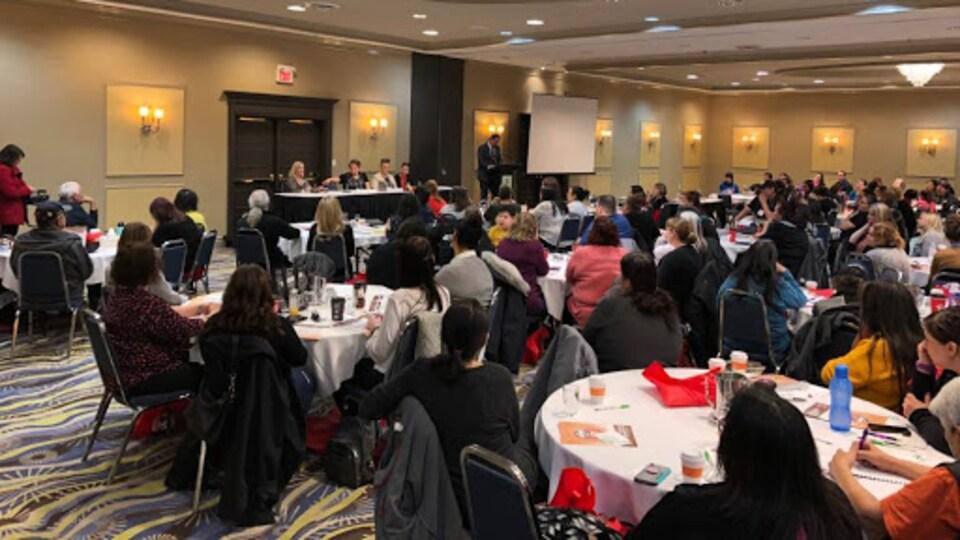 Des gens assis dans une salle et qui écoutent un groupe de panellistes