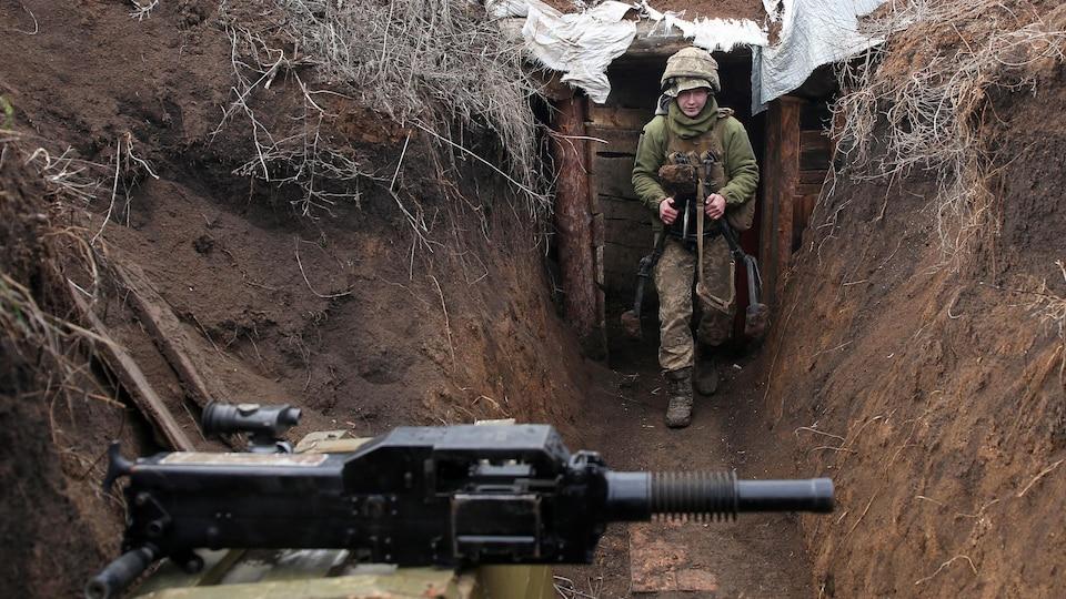 Un militaire ukrainien à l'arrière dans la tranchée. On voit une arme à l'avant-plan.