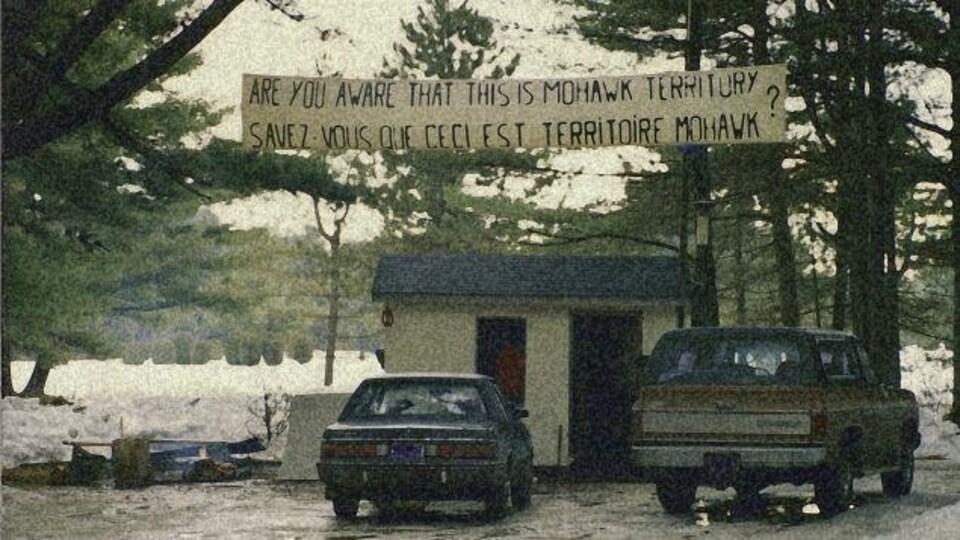 En hiver. Une bannière «Savez-vous que ceci est un terrain Mohawk?» suspendue au dessus d'un petit bâtiment devant lequel sont garées deux voitures.