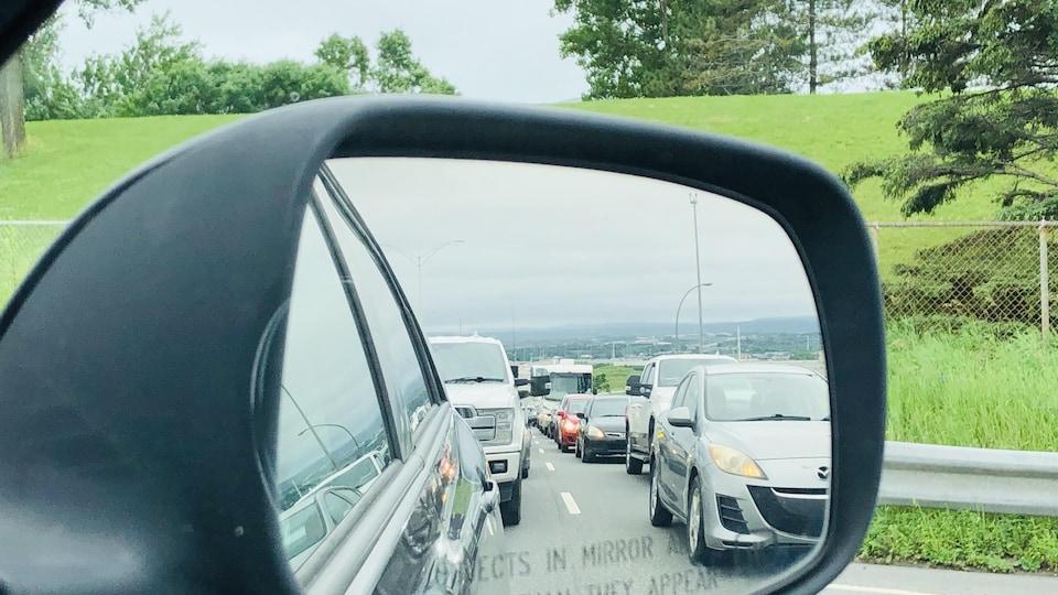 Gros plan sur un rétroviseur extérieur de voiture dans lequel on aperçoit une longue file de voitures les unes derrière les autres.