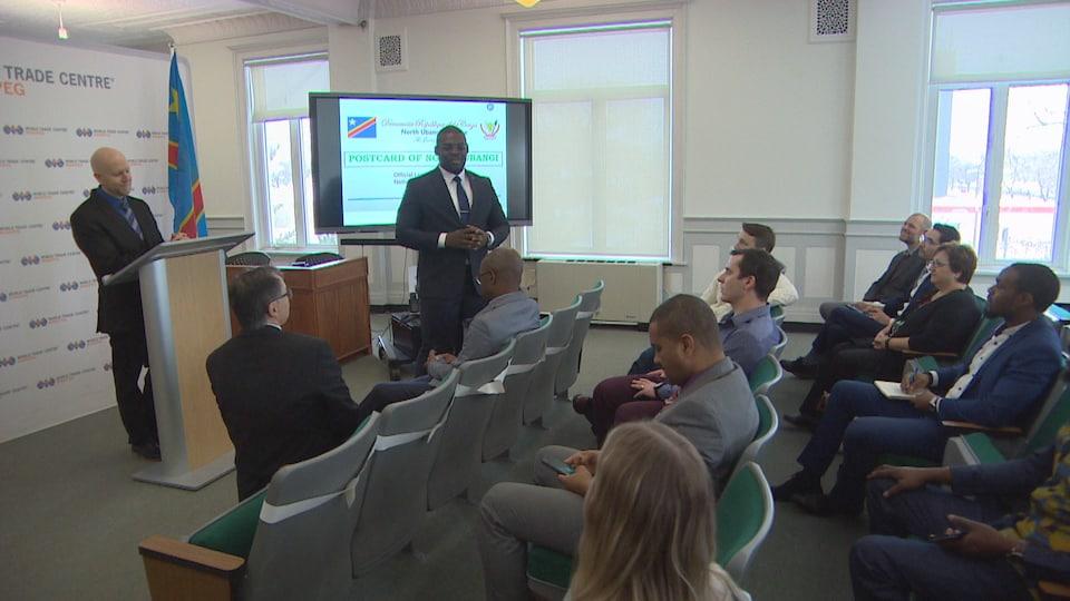 Des personnes assises dans une salle et deux hommes debout devant eux.