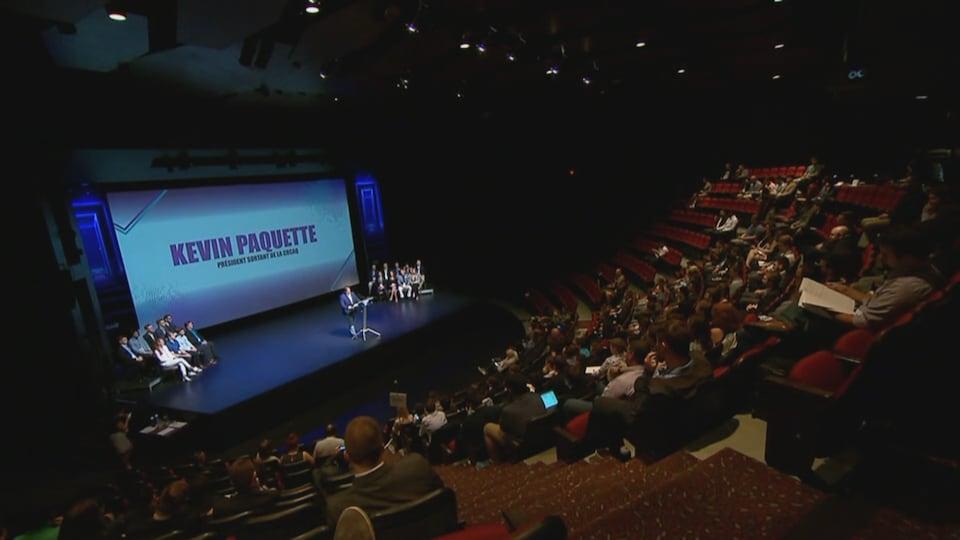 Le président de l'aile jeunesse de la CAQ prononce un discours au centre d'une scène d'un auditorium.