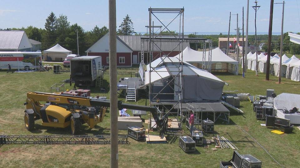 Des travailleurs s'affairent à préparer les installations, comme les chapiteaux et la scène.
