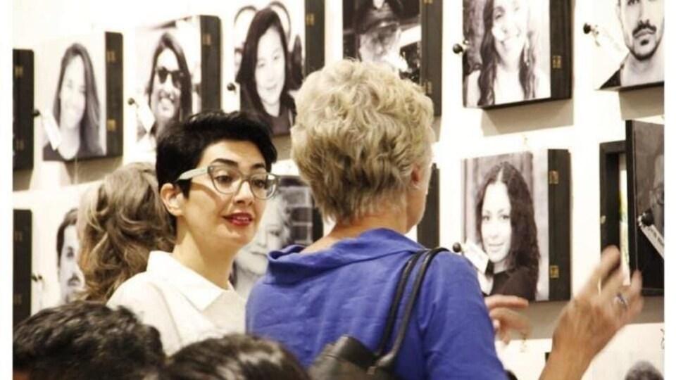 Maryam Hafizirad communique avec une femme lors d'une exposition. Derrière elles se trouvent des portraits accrochés sur un mur.
