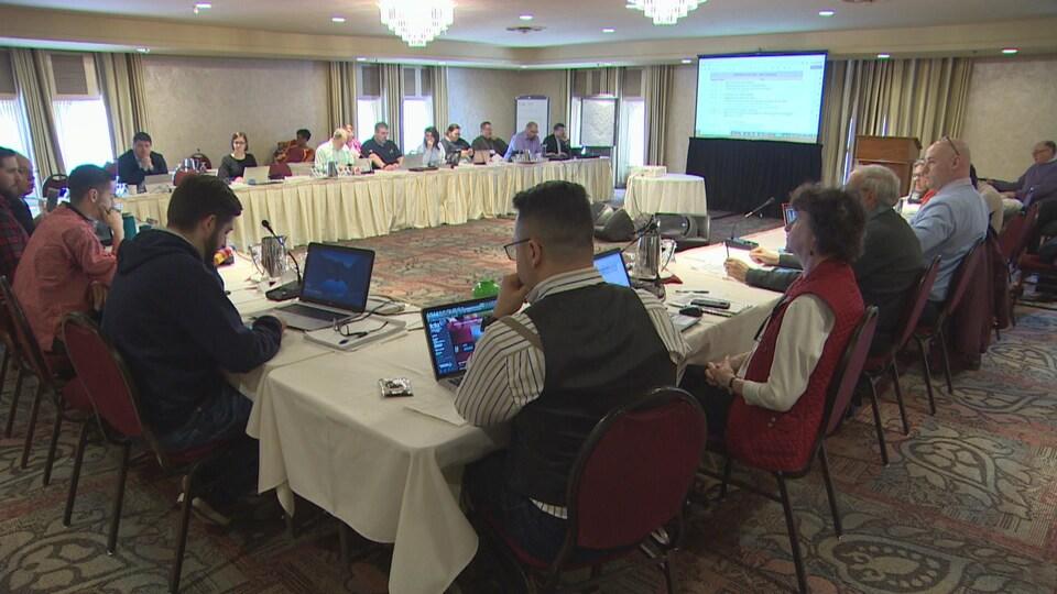 """Une grande table installée en """"U"""", dans une salle de conférence, autour de laquelle sont assis des gens, devant des ordinateurs et des micros. Au fond, un grand écran sur le mur."""