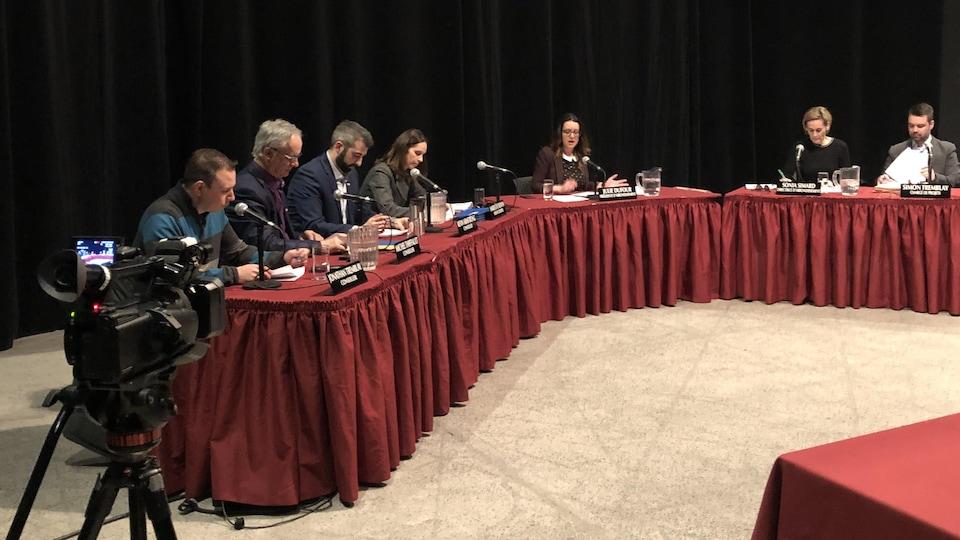 Des conseillers assis autour d'une table de délibérations.