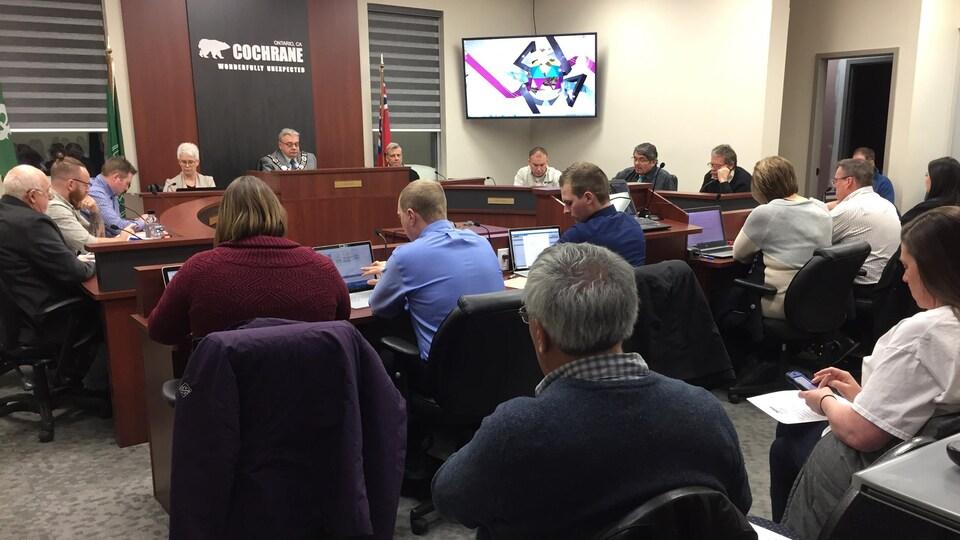 Des hommes et des femmes sont assis dans la salle du conseil municipal de Cochrane.