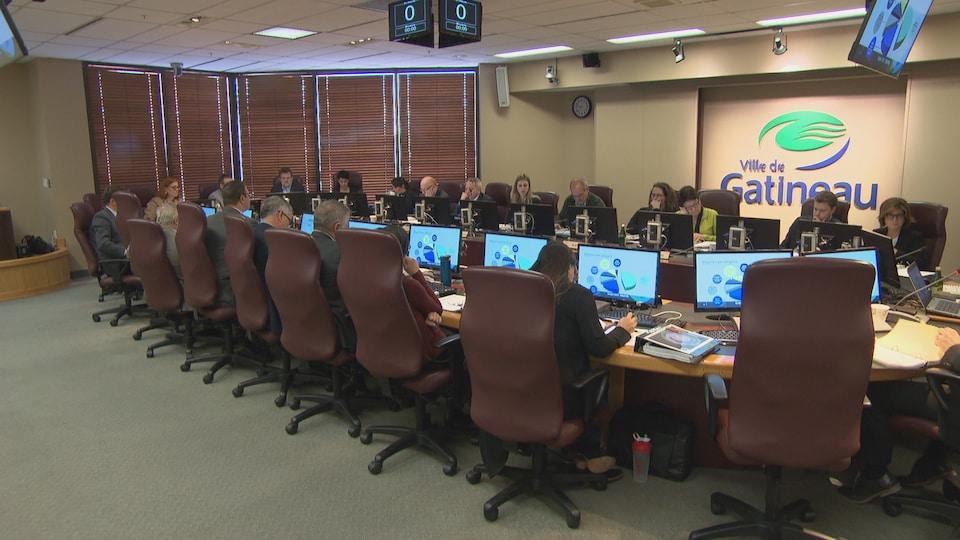 Les élus sont assis autour de la table du conseil à la Maison du citoyen
