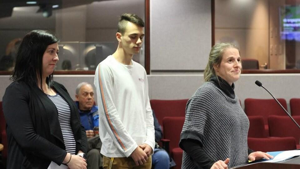Monique Bourque, Rachelle Losier-Comeau et Etienne Bélanger, président du conseil étudiant se tiennent debout derrière un lutrin.