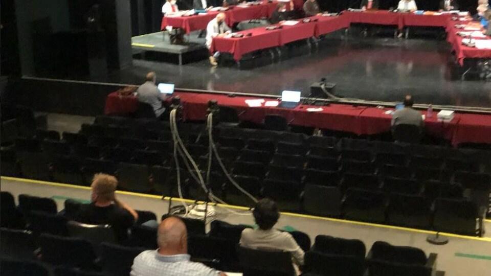 Trois personnes assises dans des estrades regardent les conseillers sur la scène.