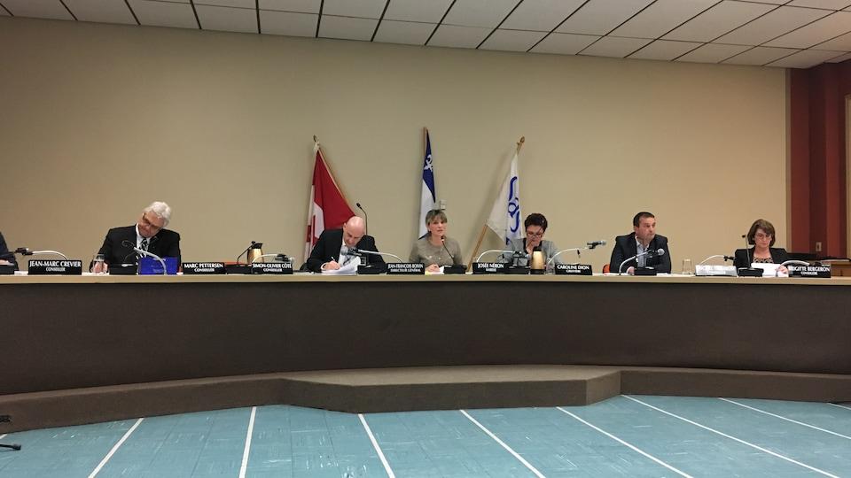 Une table ronde avec plusieurs personnes assises autour de la mairesse qui parle au micro.