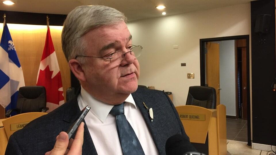 Le maire de Val-d'Or Pierre Corbeil, répond à des questions devant les micros des journalistes dans la salle du conseil.