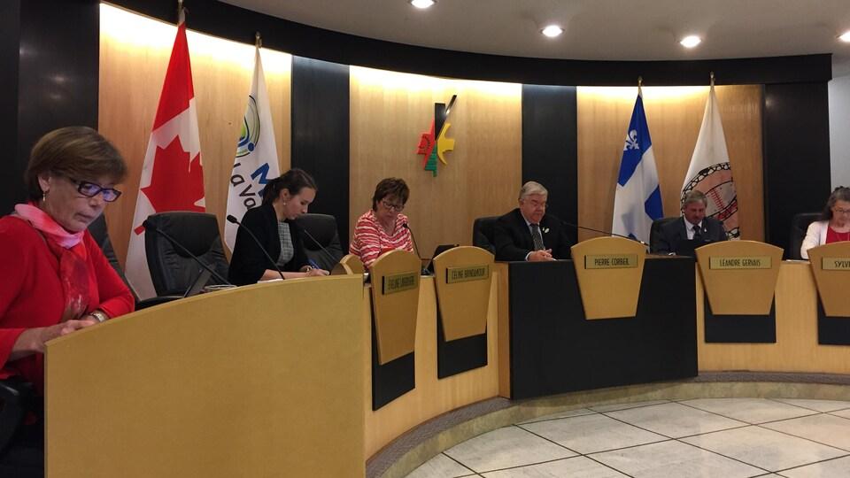 Des élus sont assis derrière leur bureau lors de la séance d'un conseil municipal.