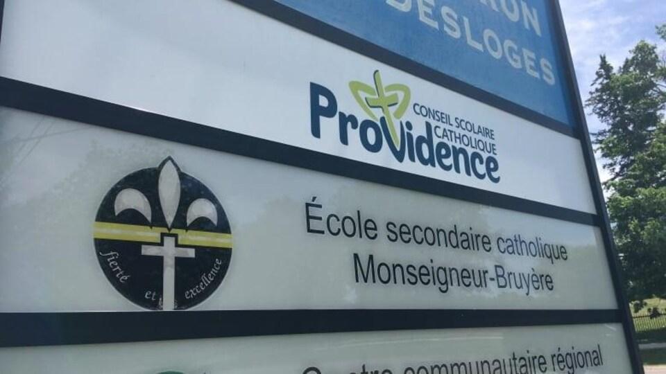 Un grand panneau avec le logo de l'école et du conseil scolaire.