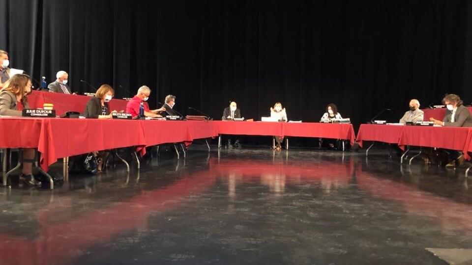 Des conseillers autour d'une table rouge.