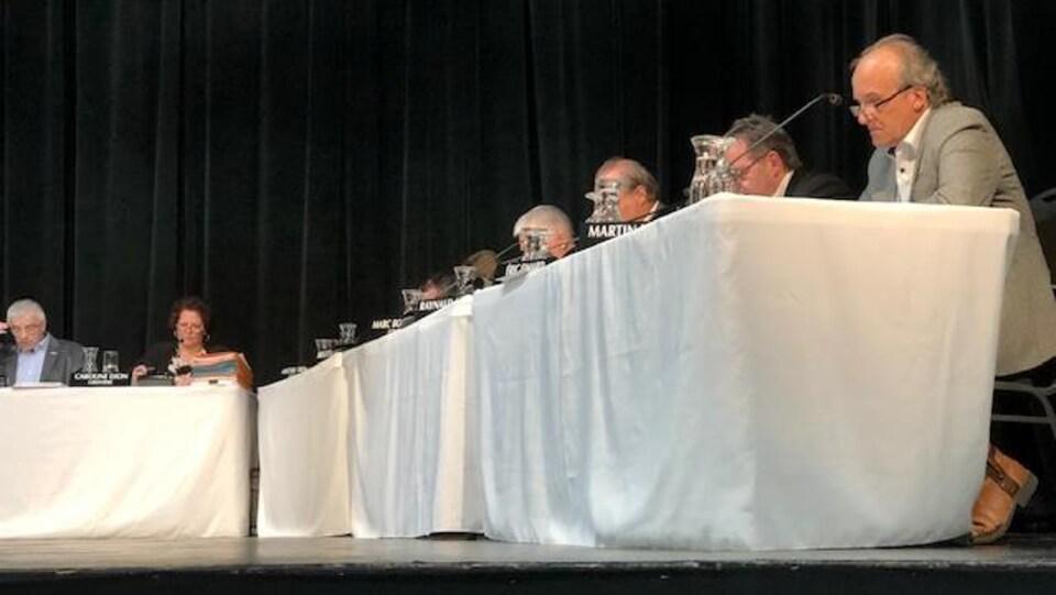 Des membres du conseil de ville assis à la table.