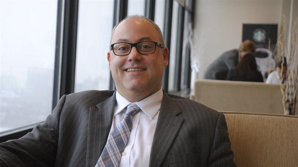 Le directeur général du Conseil scolaire Centre-Est de l'Alberta, Marc Dumont pose pour la caméra assis dans un café.
