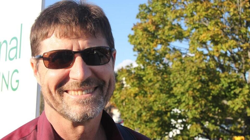Le conseiller municipal  Richard Zurawski, souriant à la caméra devant un arbre.