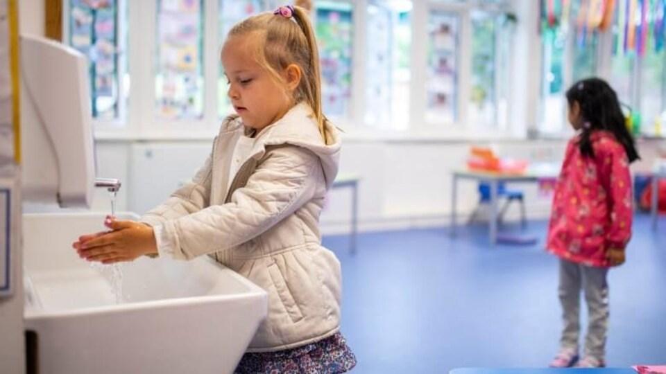 Une enfant de la maternelle se lave les mains dans un lavabo.