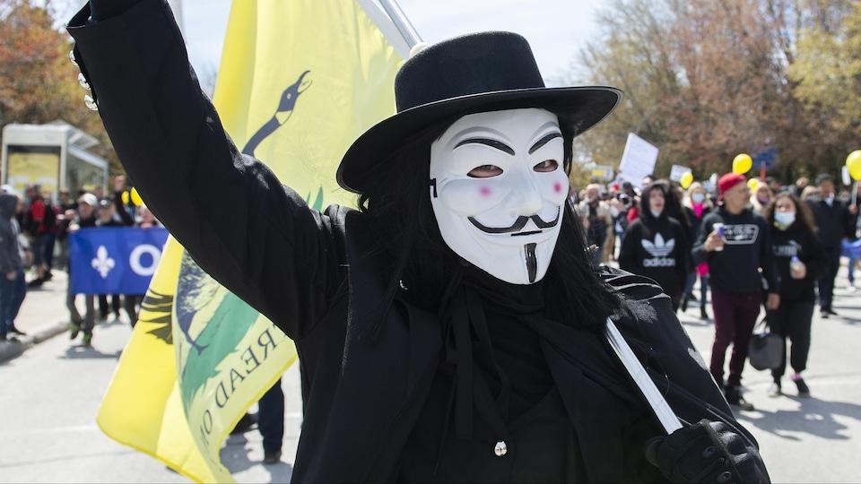 Un homme portant un masque anonyme lève le bras en signe de victoire alors qu'il manifeste dans la rue.