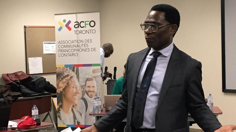 Constant Ouapo, président sortant de l'ACFO Toronto, debout pendant une réunion