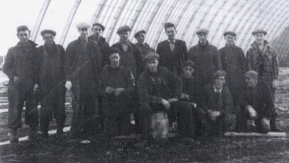 Des hommes posent alignés sous la structure en construction de l'aréna sur une photo en noir et blanc datant de 1953.