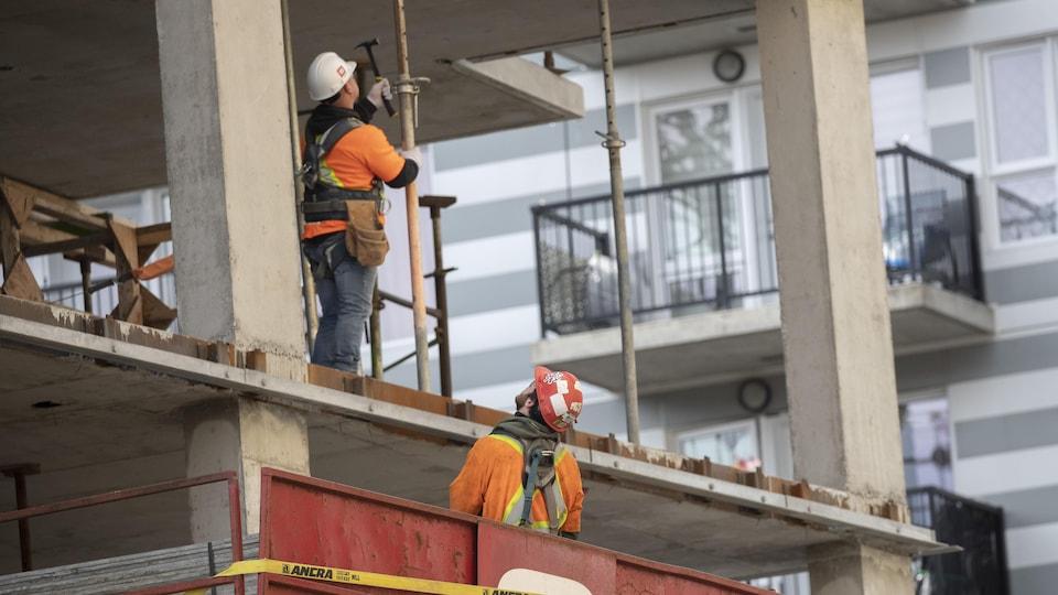 Deux travailleurs de la construction sur un chantier résidentiel.
