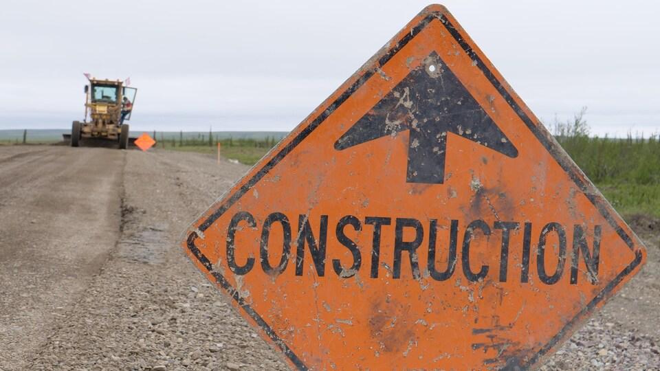 Un panneau de construction très usagé sur une route de gravier devant un camion de construction qui gratte la route au loin.