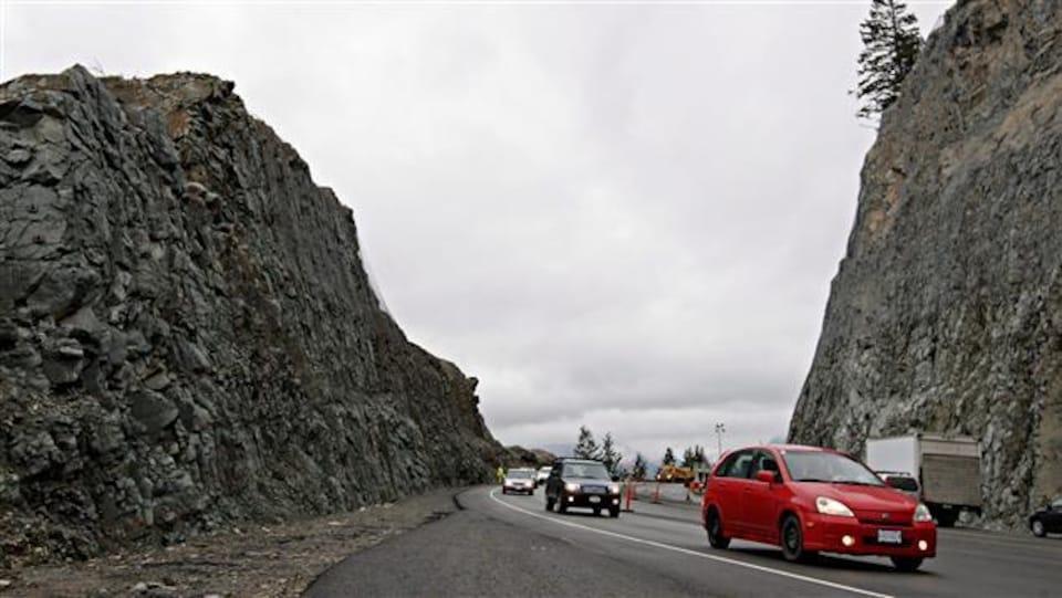 Quatre voitures circulent sur une route asphaltée. Des deux côtés de la route, il y a un flanc de montagne rocailleux.