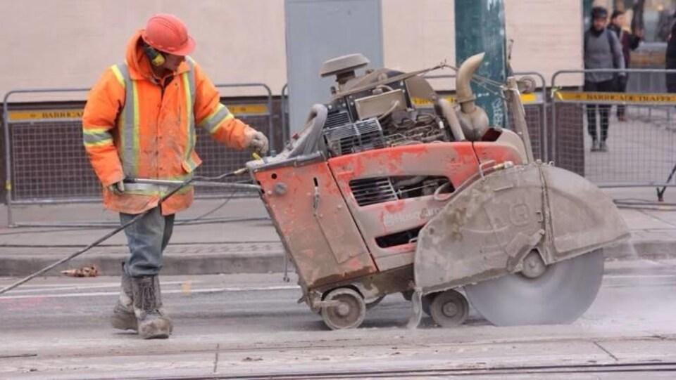 Un ouvrier procède à la réfection d'une route.