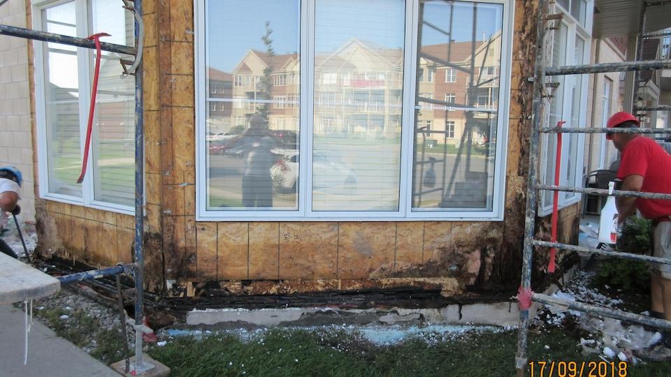 Un homme répare la structure de l'immeuble.
