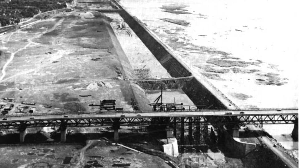 Le canal en construction, le long du fleuve, traversé par deux ponts.