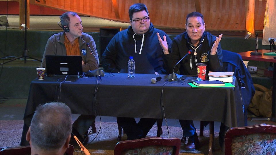 Trois hommes à une table lors de la consultation.