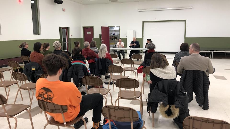 Des gens assis dans une salle communautaire.