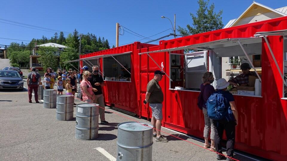 Une file de clients qui attendent pour être servis devant un comptoir restaurant installé dans un conteneur.