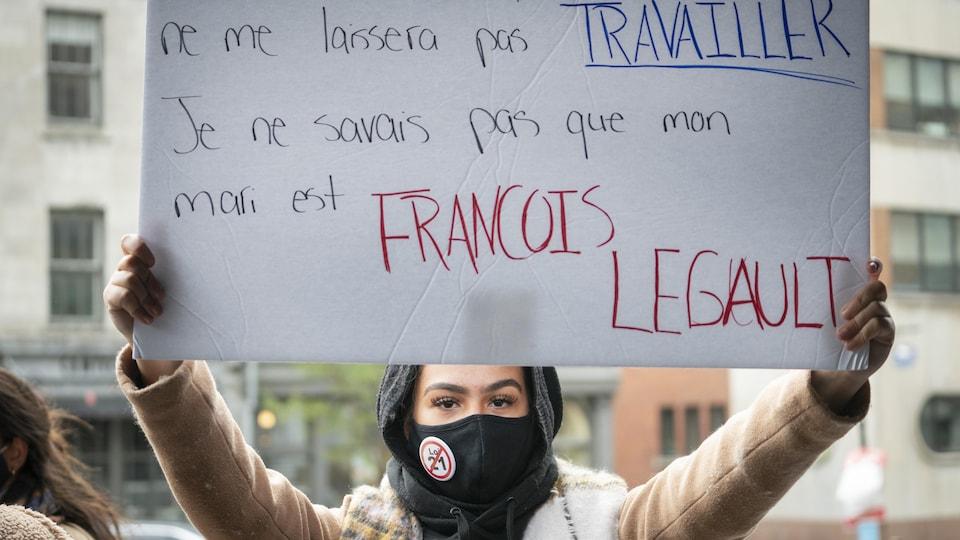 Une femme tient une pancarte qui conteste la loi 21.