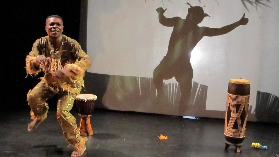 Patience Fayulu entrain de danser devant deux tambours et un fond blanc sur lequel est projeté l'ombre d'un humain.