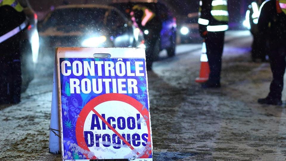 Des véhicules avancent lentement à un barrage routier, un soir d'hiver, sous la supervision de policiers.