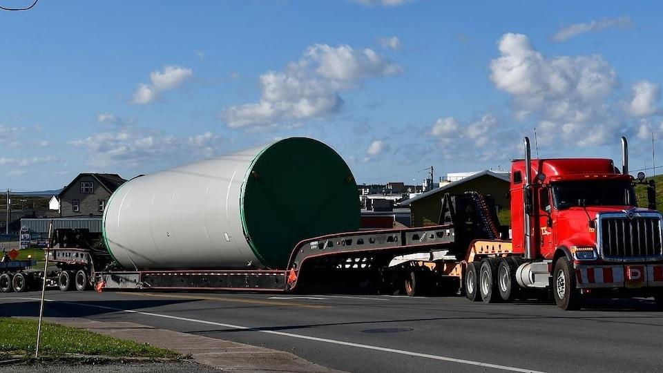 Un camion transporte une section de mat d'une éolienne.