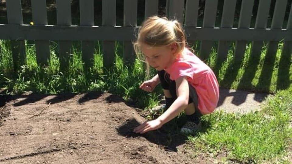 Une jeune fille plante des graines.