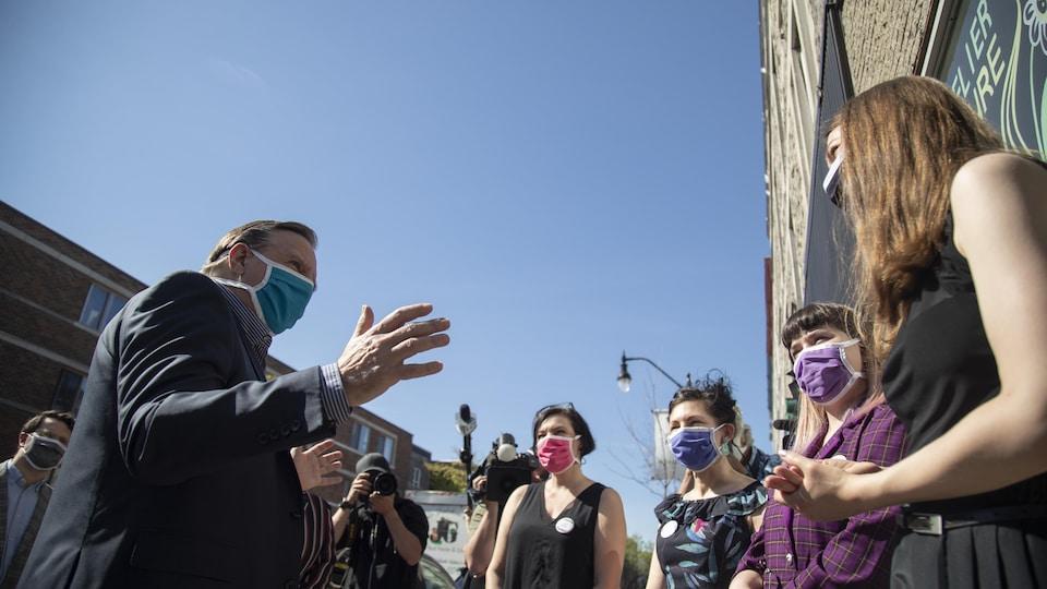 La rencontre se déroule à l'extérieur, sur le trottoir. Tous portent des masques.