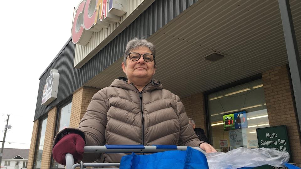 Un femme sortant d'une épicerie avec son panier de provisions.