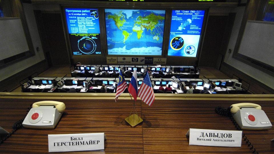 Un bureau avec deux téléphones, des petits drapeaux, avec un écran géant à l'avant.