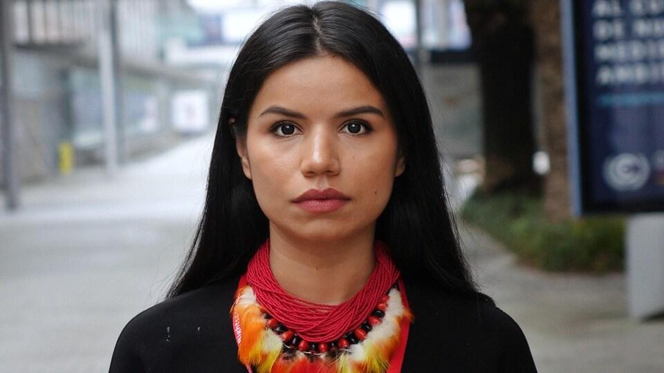 Portrait de Nina Gualinga qui regarde droit devant elle.