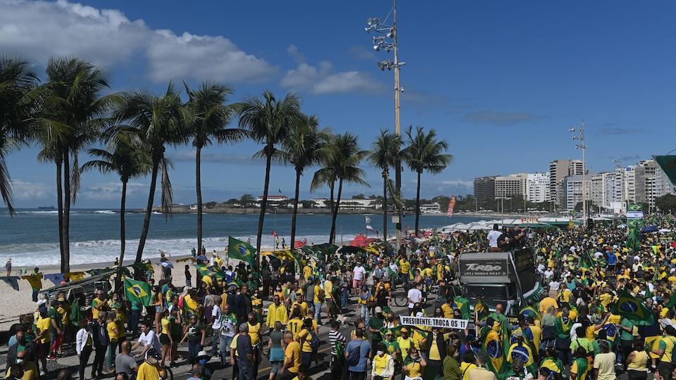 Une foule de manifestants défilent le long d'une plage.