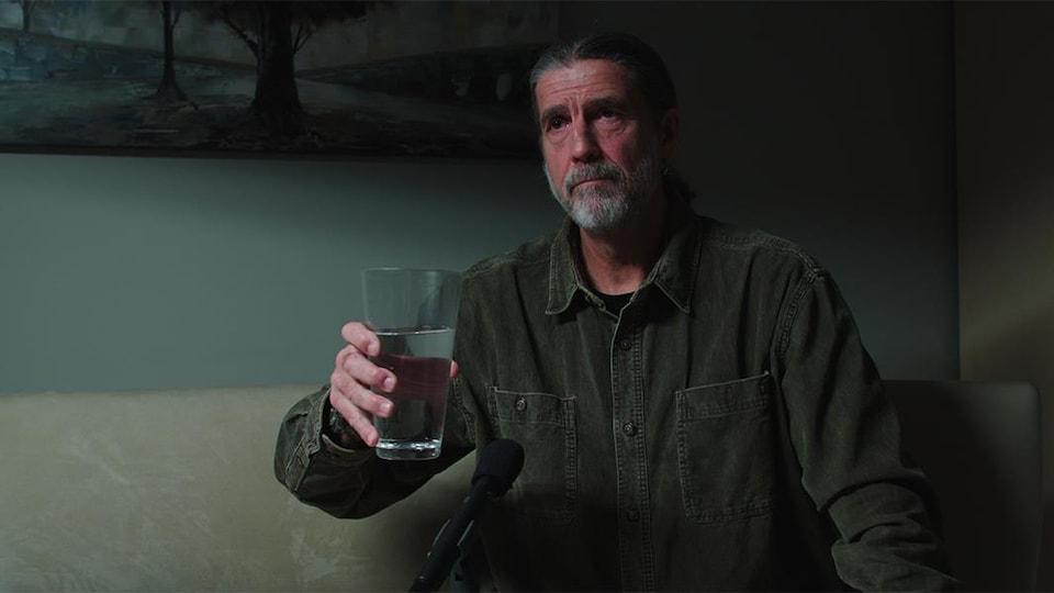 Un homme tient un verre d'eau et regarde vers la gauche.