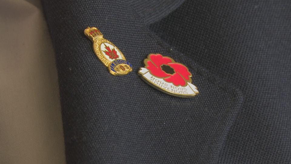 """Un insigne en forme de coquelicot est attaché sur le veston de Réginald Basque. Il est écrit: """"Nous nous souvenons""""."""