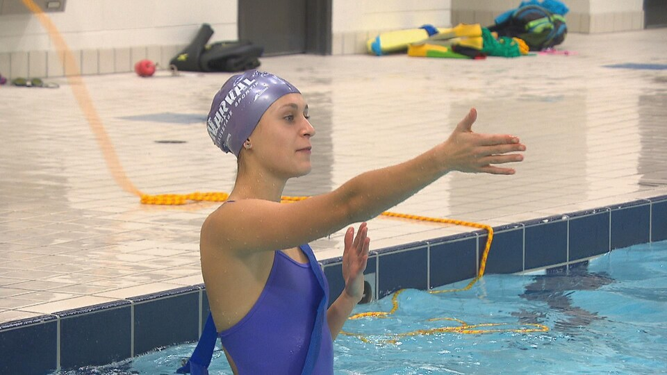 Une jeune femme est dans une piscine et donne des consignes.