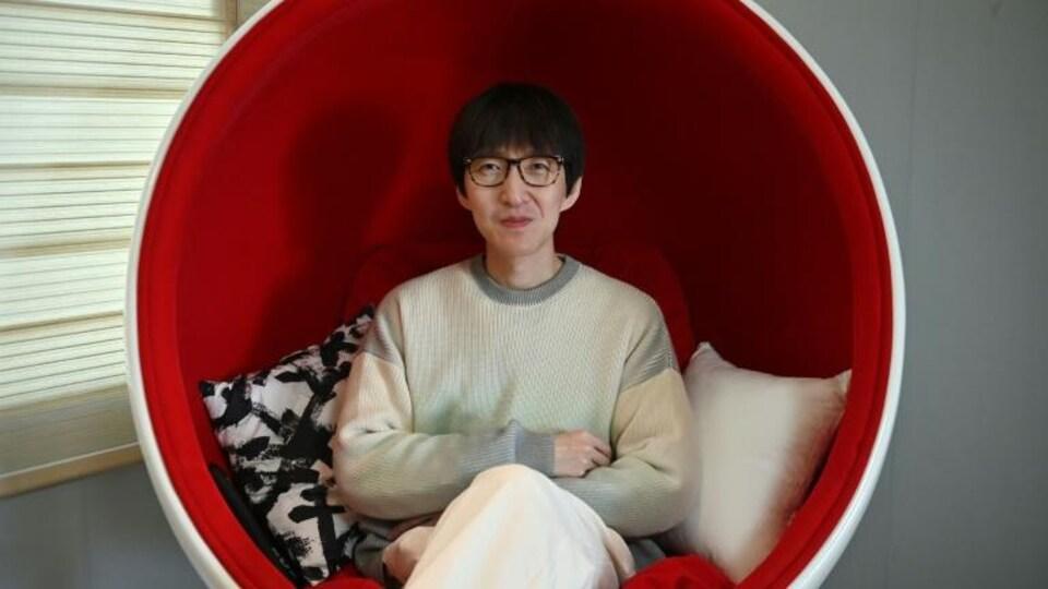 Un homme assis sur un fauteuil moderne rond arborant le rouge et le blanc.
